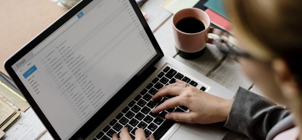 girl sitting at desk typing on laptop