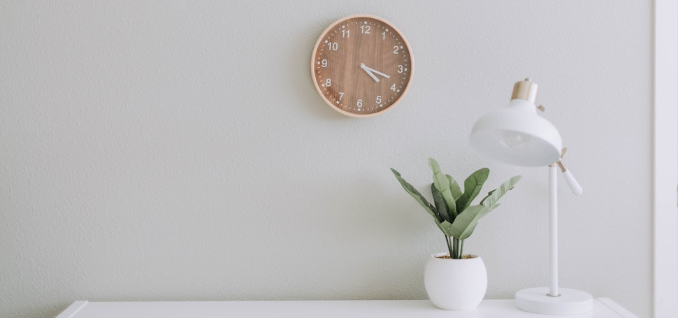 a modern office with light grey walls, a wood clock, white desk, white lamp, and plant
