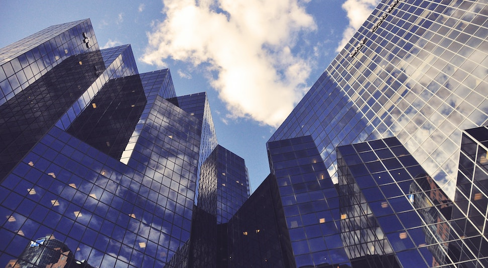 glass skyscrapers and the blue sky above - difference between recruiters and headhunters